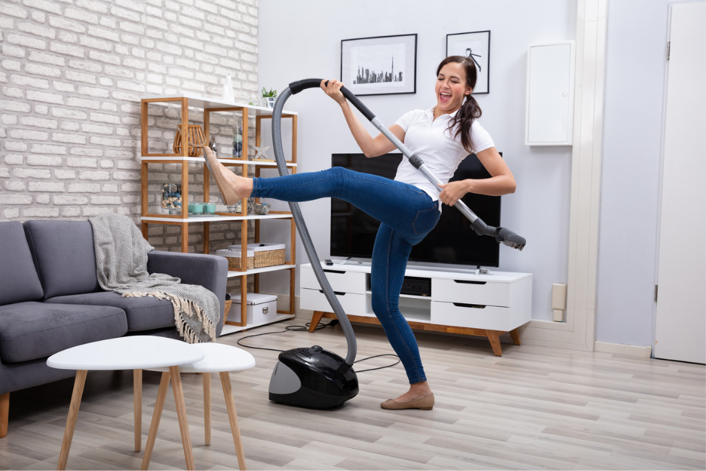 Happy woman with vacuum cleaner