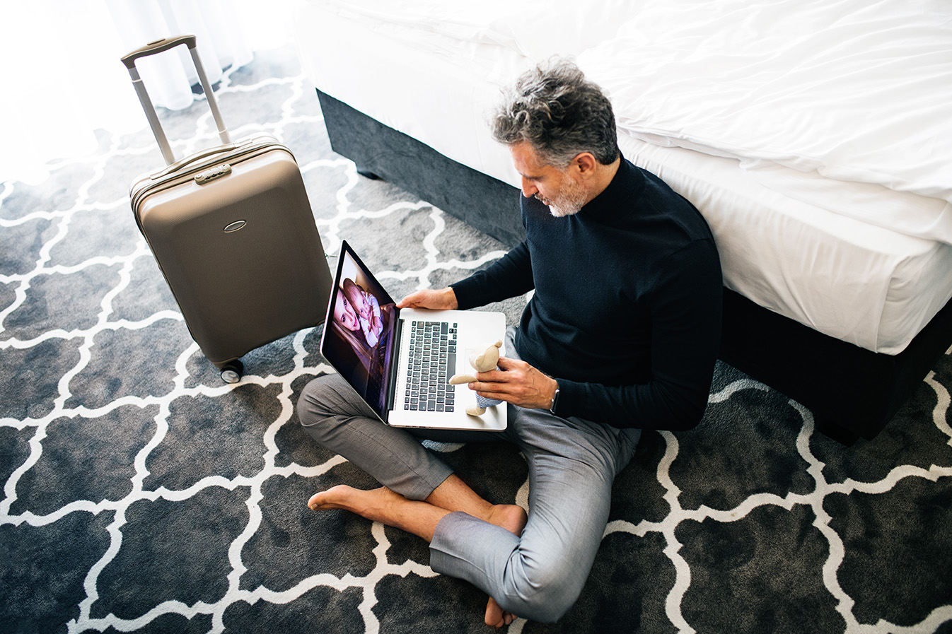 man with laptop and suitcase in an apartment