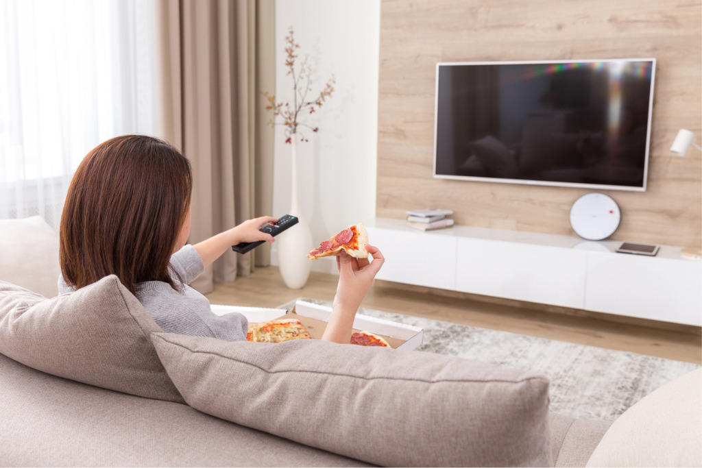 Woman eating pizza and watching tv